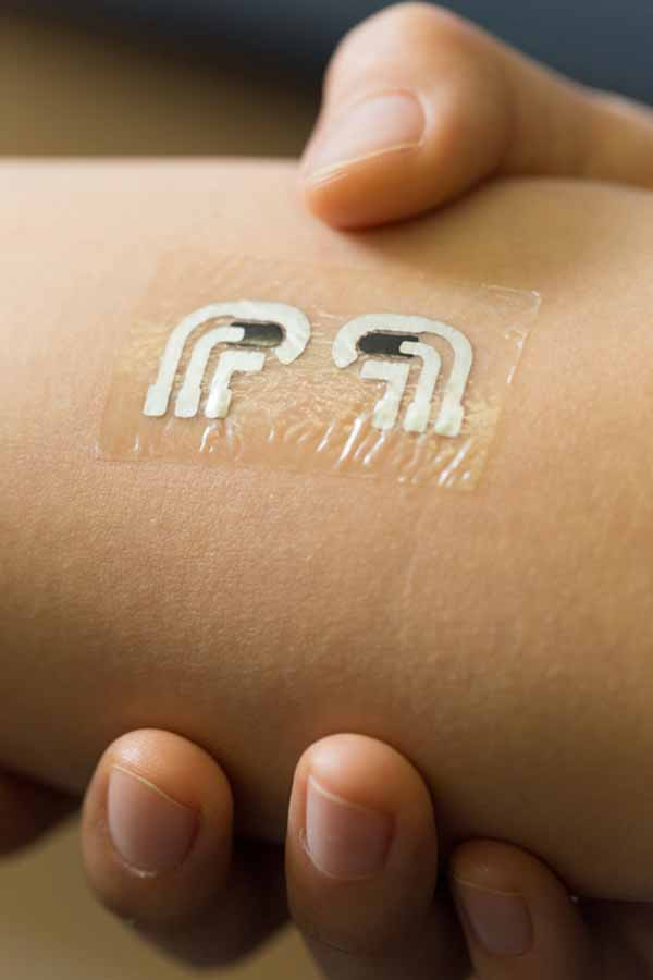 Nanoengineers at the University of California, San Diego have tested a temporary tattoo that both extracts and measures the level of glucose in the fluid in between skin cells.  The device is flexible and easy to wear.  Credit:  Jacobs School of Engineering/UC San Diego.